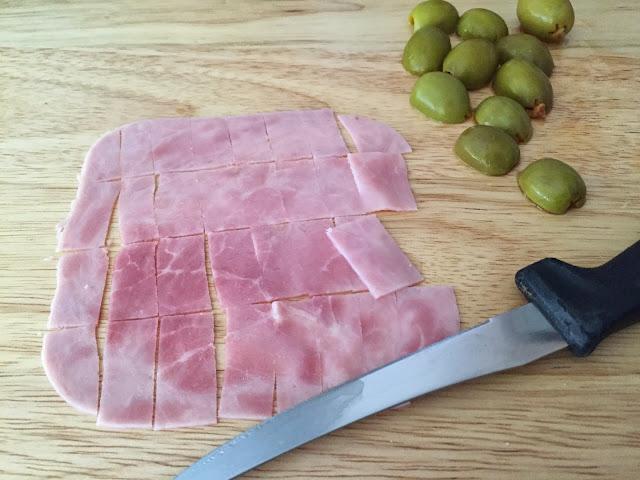 Mini tostas de jamón, queso y aceitunas. Cortando el jamón y las aceitunas.