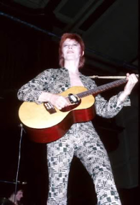 David Bowie playing guitar as Ziggy Stardust
