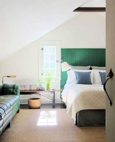 bedroom with sisal rug beadboard, green headboard, a green leather sofa with a plaid throw, dark wood floor, a bench style nightstand and a small window