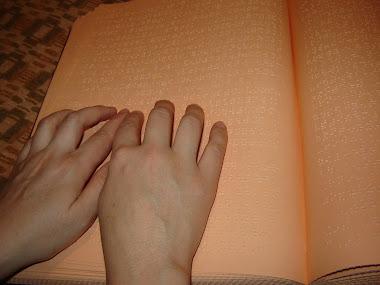 Książka brajlowska czytana przez osobę niewidomą
