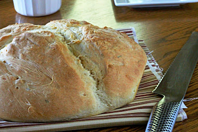 loaf of potato bread on a napkin with a bread knife next to it