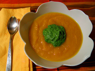 Bowl of Orange Carrot Soup with Dollop of Green Pesto