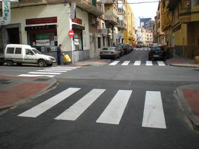 Vista de paso de peatones con vado de color rojo contrastado con el pavimento gris del resto del acerado.
