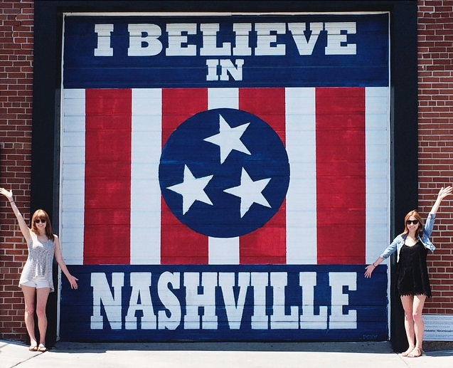 Twins standing in front of I Believe in Nashville mural