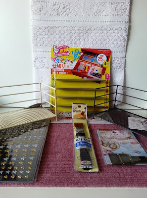 Selection of discount items from Daiso, including a table runner, sticker sheet, wire shelves, a paint brush and a packet of metal crafting frames.