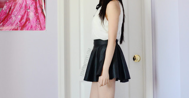 Side view of Dresslink's white and black ribboned off-shoulder blouse/vest, worn with a faux leather skater skirt.