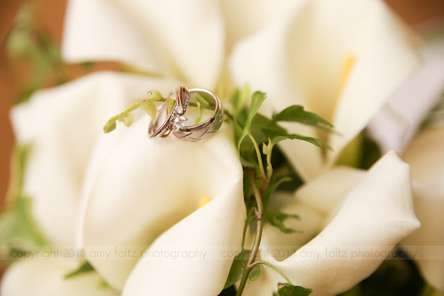 photo of wedding rings on white calla lillies and ginkgo leaves
