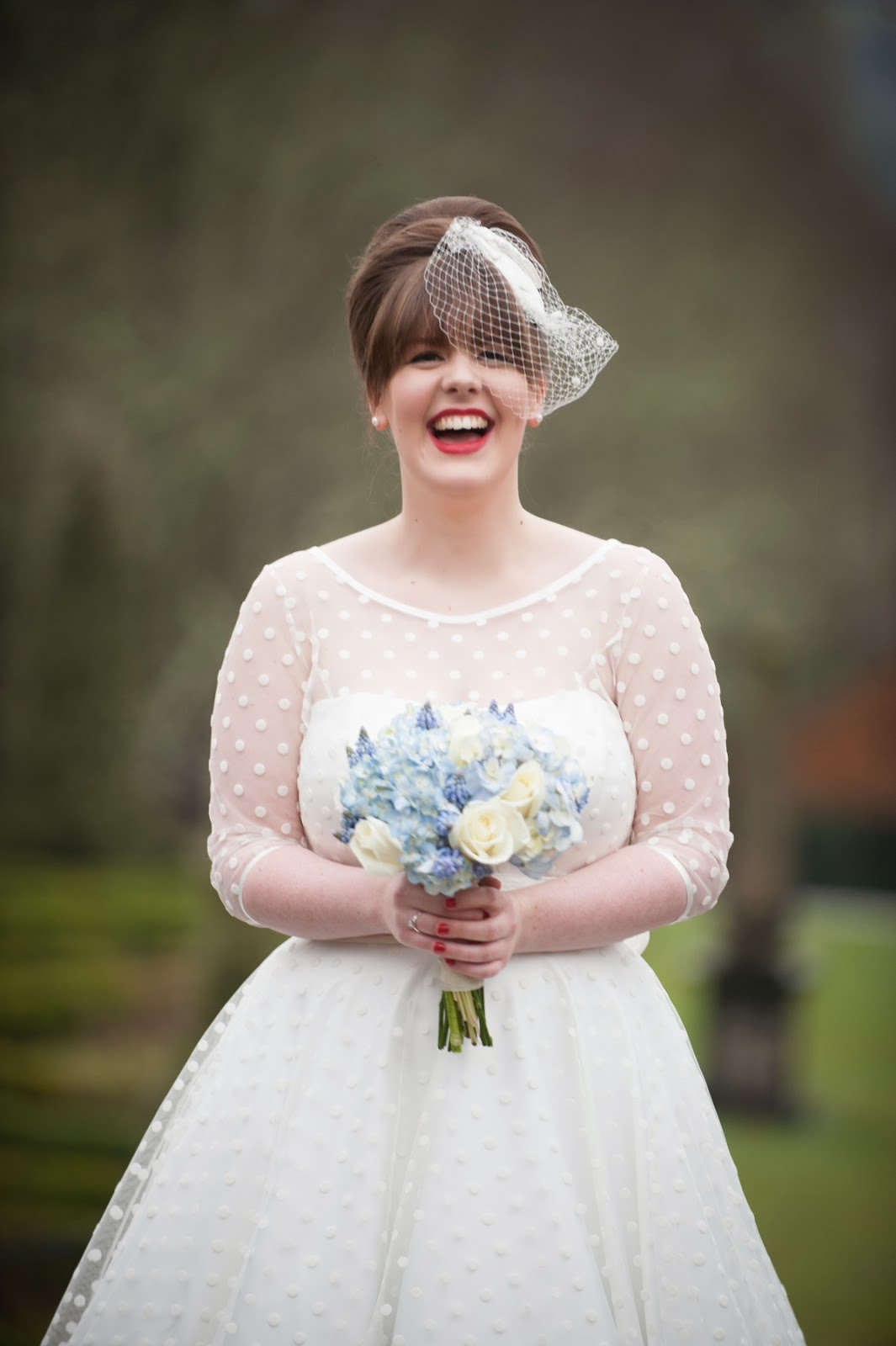 Bride in fifties style shorter length dress with polka dots holding bouquet of blue flowers
