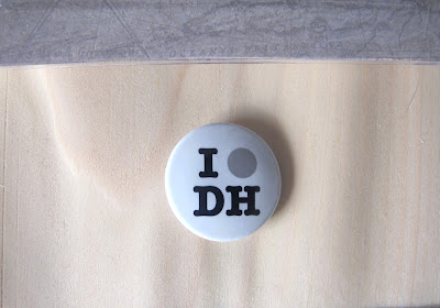 Badge saying 'I [spot] DH' on top of a sheet of wood veneer.