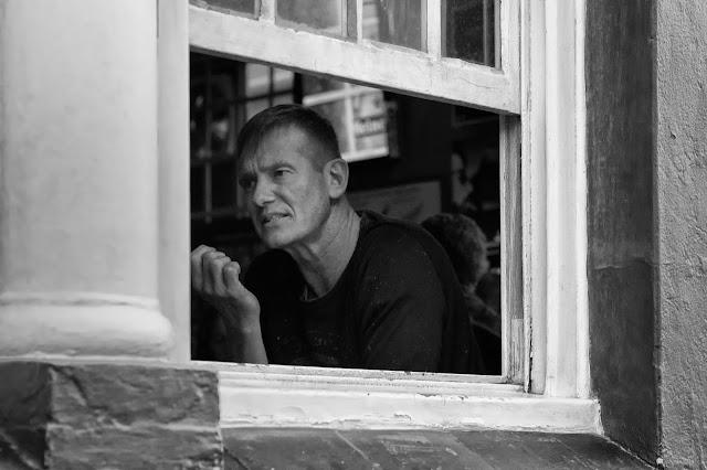 A street photograph shot through a window - a man in conversation.