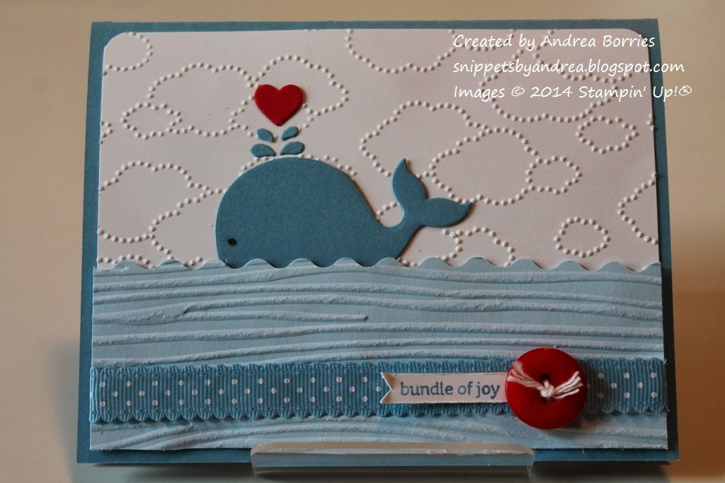 Card with a die-cut whale, embossed waves and clouds and a red button embellishment.