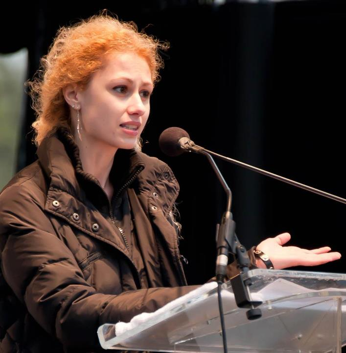 Photograph of Cristina Rad speaking at a conference, in front of a transparent podium, with a high end microphone attached, all against a black background, with long curly reddish hair pushed back and stylish jacket; she gestures to make a point.