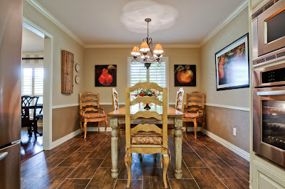 a traditional dining room with neutral hues and wood accent floor surrounded with bright fruits painting