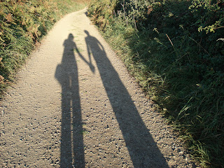elongated shadow of couple holding hands