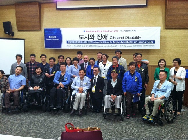 image of group of about thirty people, some in wheelchairs, posing in front of room for photo