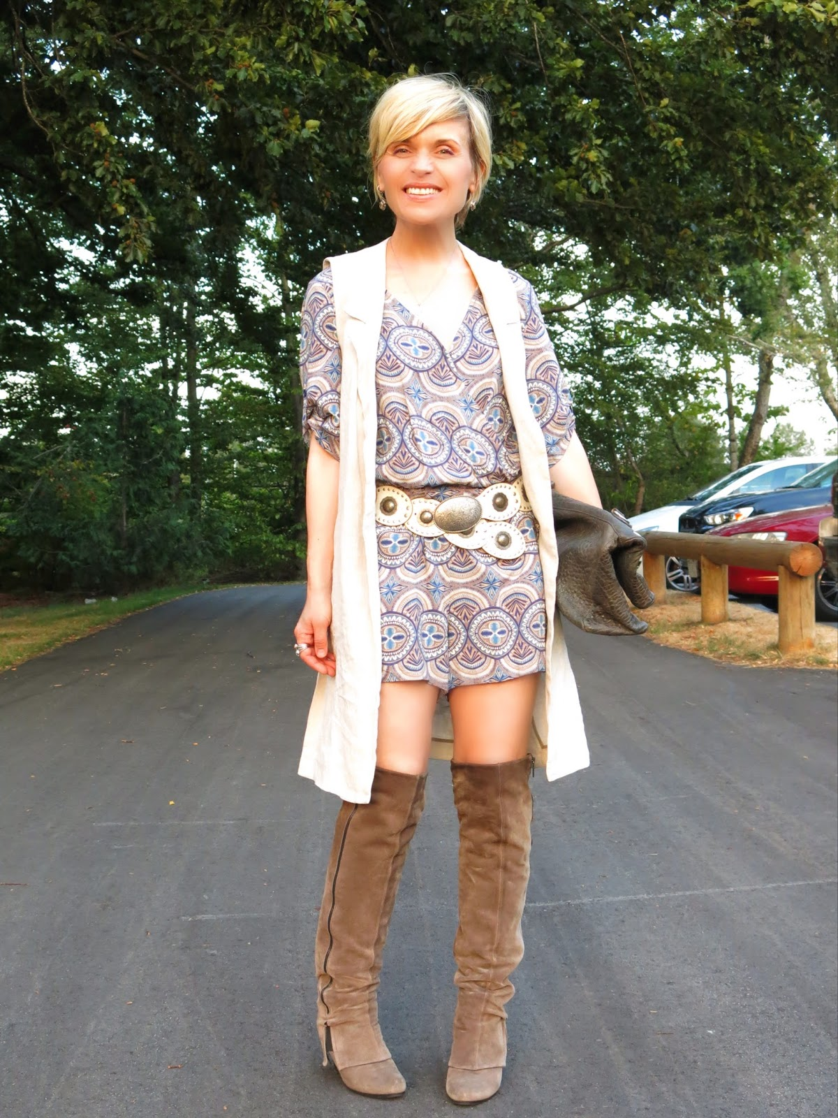 styling a patterned romper with a sleeveless coat, concho belt, and over-knee boots