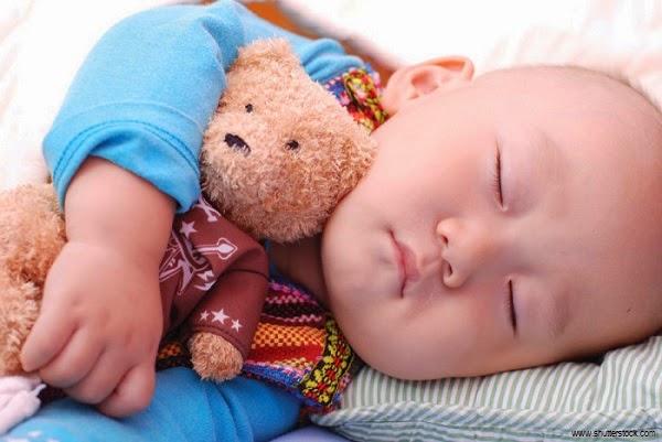 Bébé garçon  qui dort avec doudou