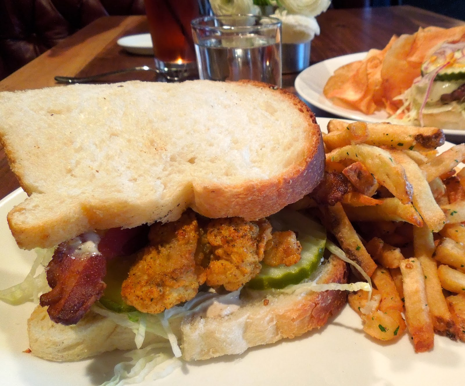 This lunch sandwich of fried oysters, bacon and other tasty items is a ...