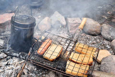 campfire with billy sausages and bread toasting in a wire cage