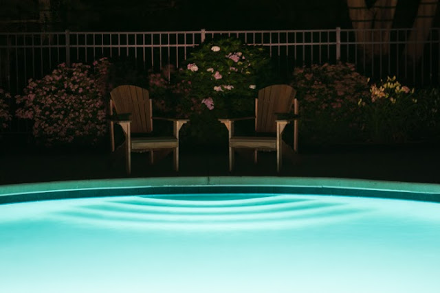 Adirondack chairs by a pool at night