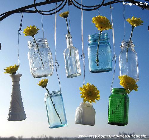 Kleničky pověšené na stromě a v nich jsou květiny