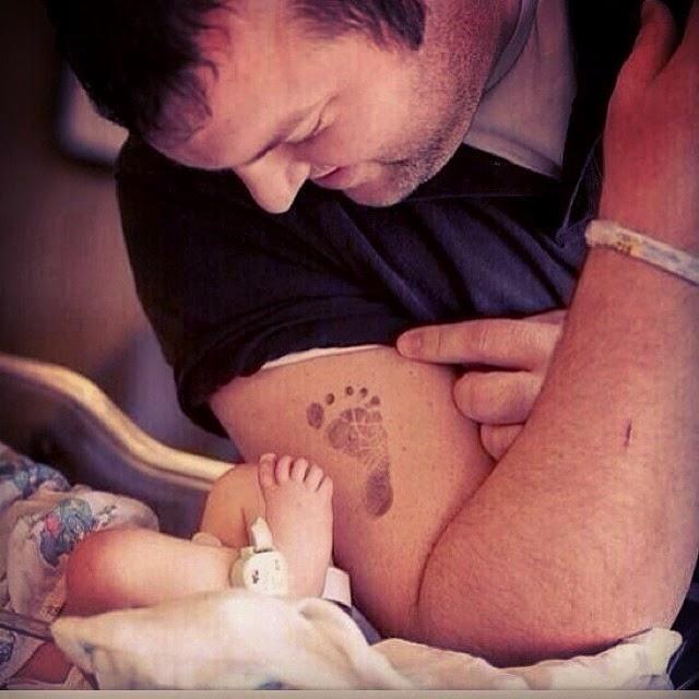 Tatuaje de un padre que adora a su hijo recién nacido