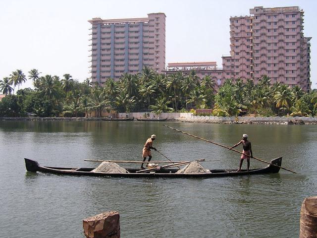 Керала Индия рыбаки на лодке на фоне города