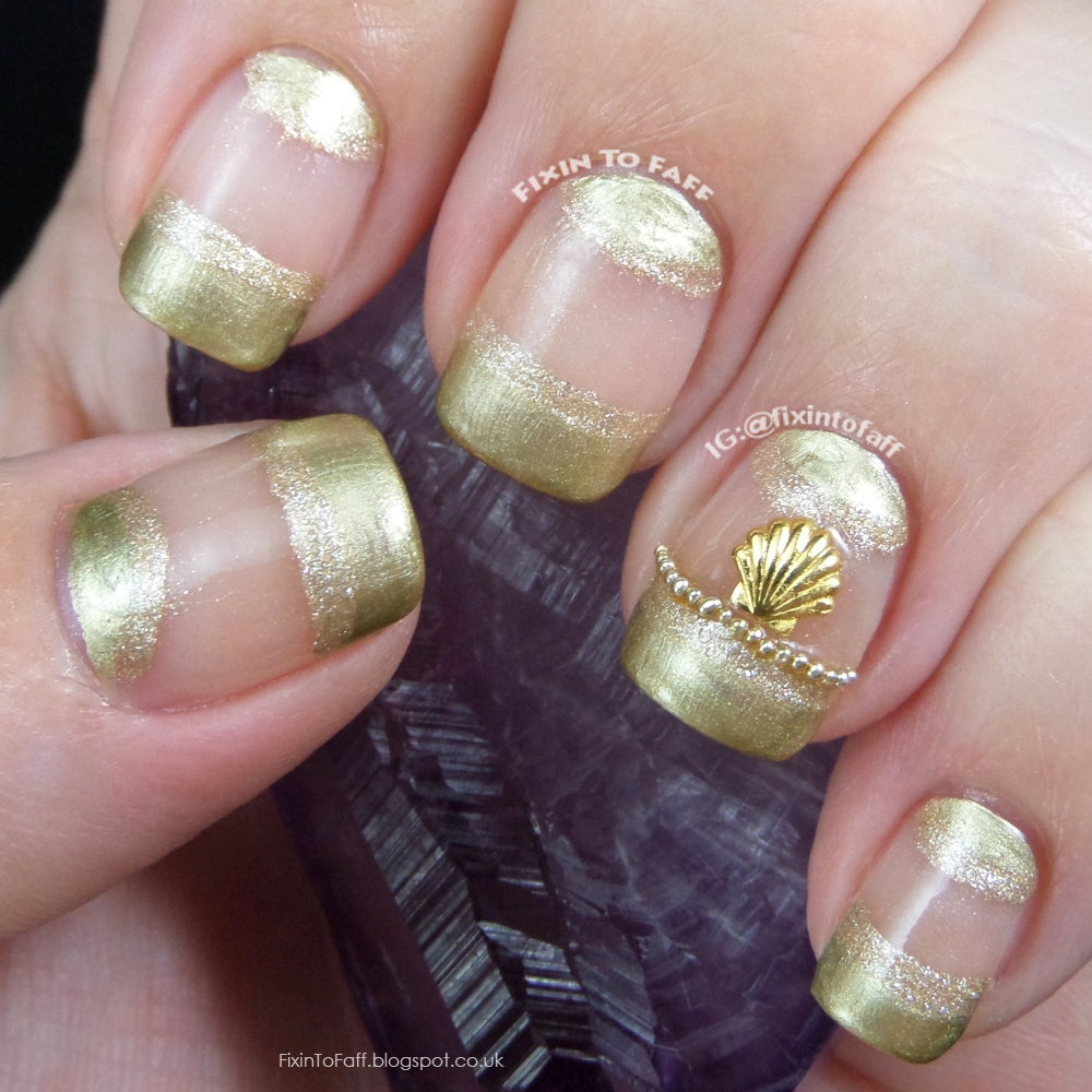 Gold french tip and half moon nail art with 3D microbead and shell stud accents.