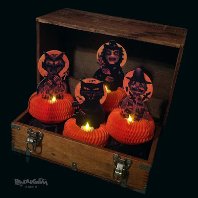 Using battery-operated tealights, the Beasties (witch, scarecrow, devil, and black cat) are shown here lighting up an old crate in the dark.