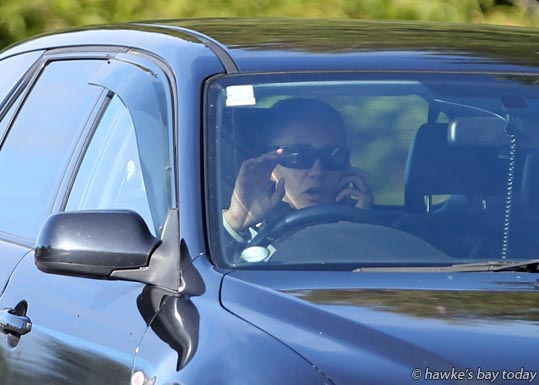 Driver using a cellphone, mobile phone while driving, Havelock Rd, Havelock North, one of four in one hour, late morning photograph