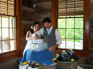 Bride and groom cut the cake in a cabin. Nearby a groom's cake is shaped like a mountain.