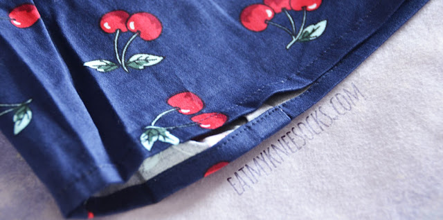 Details on the FINEJO cropped cherry print collared shirt from Dresslink, featuring a crisp fold-over collar, buttoned front, and boxy sleeveless fit.