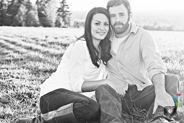 black and white of a couple sitting in a field