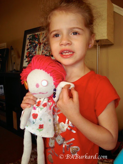 Granddaughter holding the doll she designed with her mother