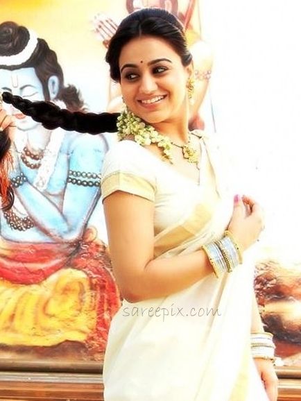 Aksha smiling photo in white traditional saree