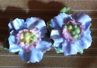 A pair of china earrings in the shape of blue flowers