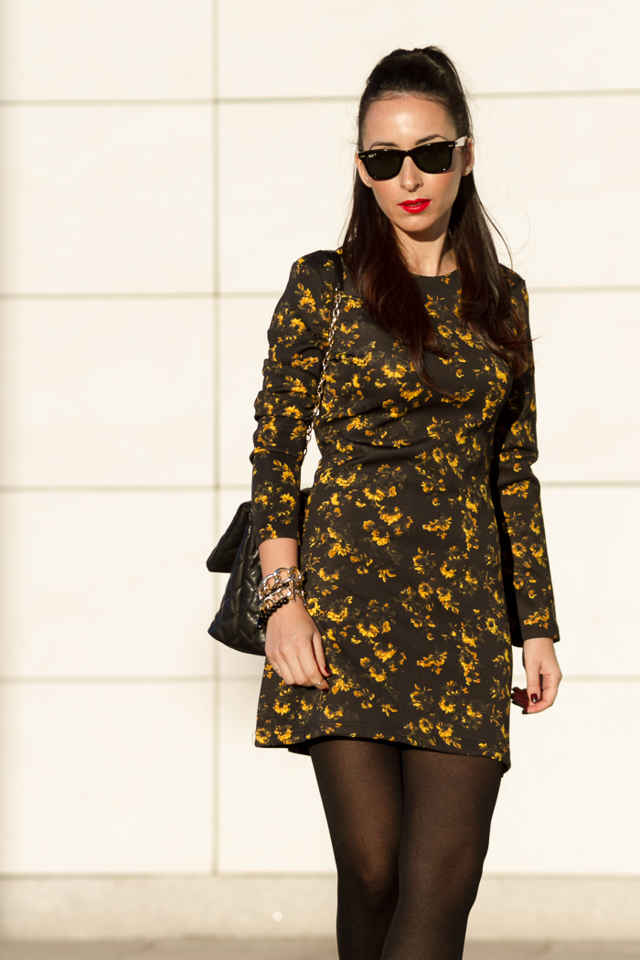 Estilo lady vestido corto en color mostaza y negro de neopreno con bolso acolchado de Zara con coleta y labios rojos