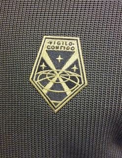 Close-up of XCOM insignia patch on Spyder sweater knit jacket