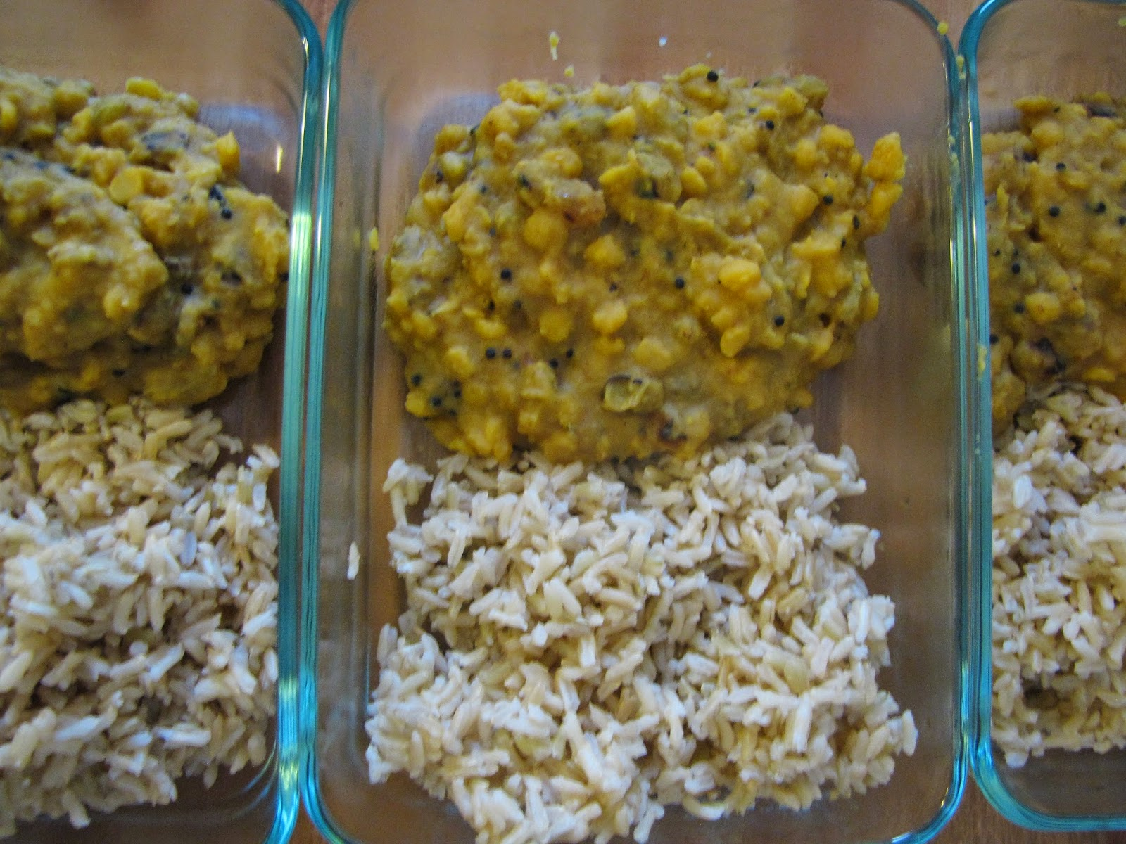 A packed lunch of brown rice and cholar dal in a pyrex dish