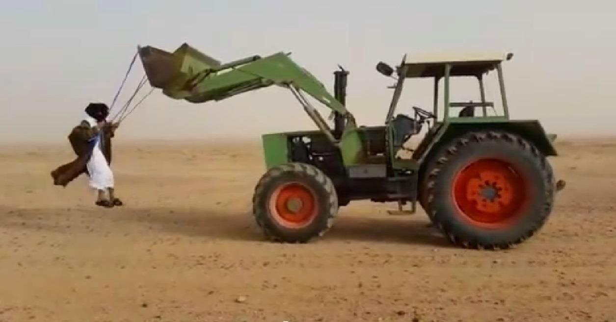 مغامرون سعوديون يتدلون من أعلى الجرار في الصحراء