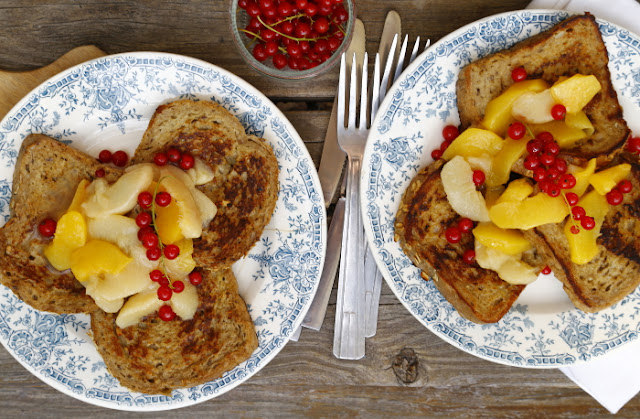 A plate of French toasts and fresh fruits on a wooden background