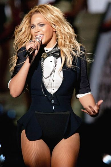 Fashionista and singer Beyonce glamorous style outfits mini swimsuit black suite and tie concert look.