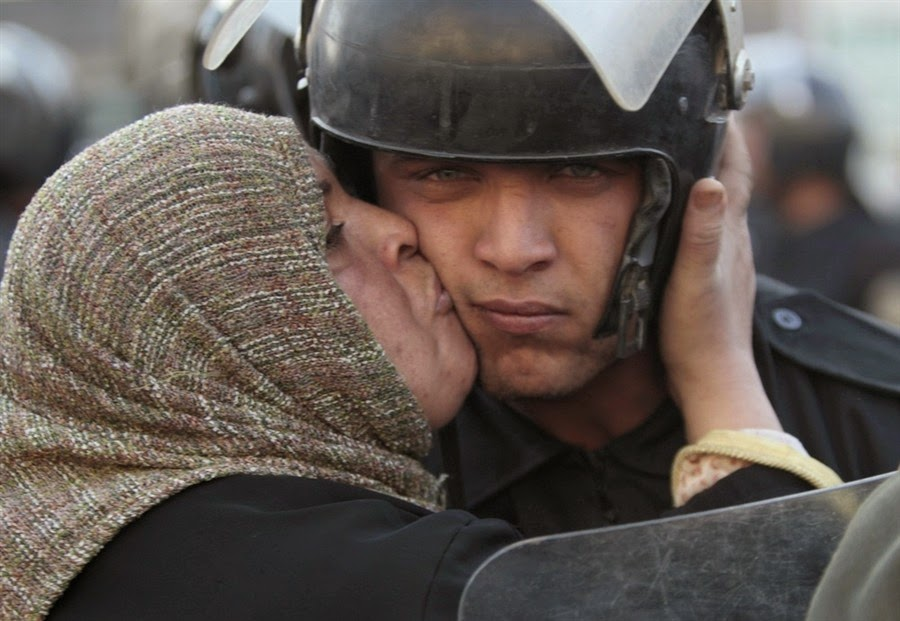 35 moments of violence that brought out incredible human compassion - egyptian woman kisses a policeman during the revolution