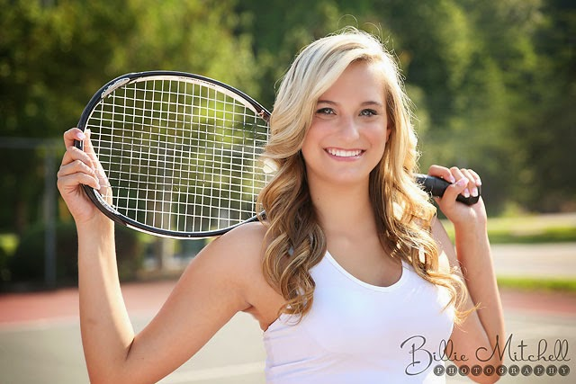 blonde senior girl holding tennis racket behind her head on her shoulders