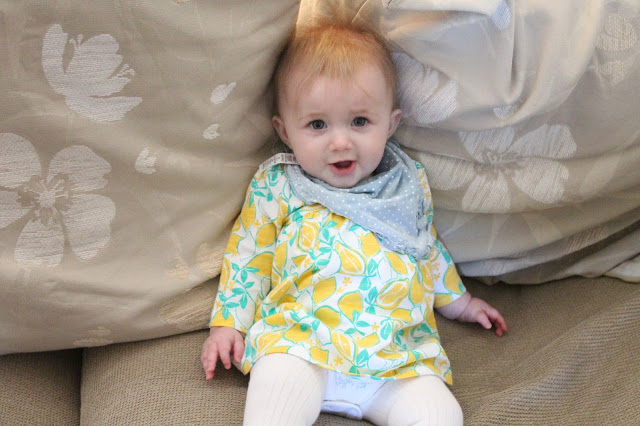 baby wearing lemon print dress from Next with blue denim look bib and white tights