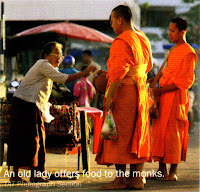 An old lady offers food to the monks