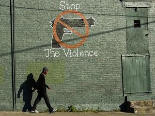Man walks past graffiti that say stop the violence.