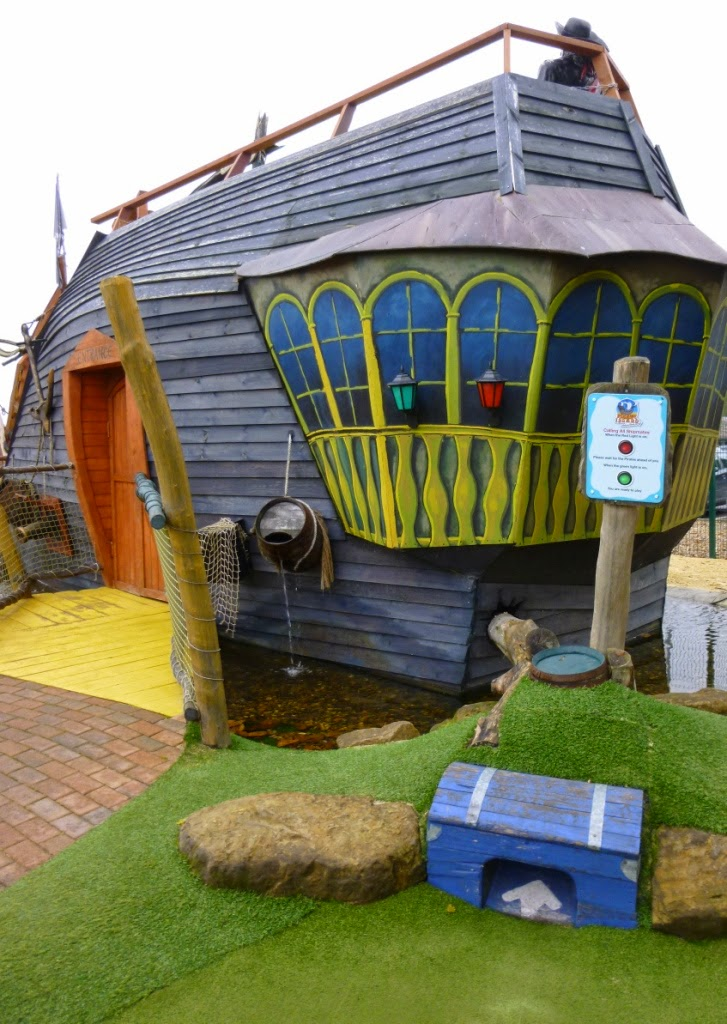 You begin playing the first of two minigolf holes aboard the pirate ship at Pirate Island Adventure Golf OUTSIDE! From the tee you have to successfully get the ball up the pipe beyond the blue crate. And if you're lucky you'll be rewarded with an ace