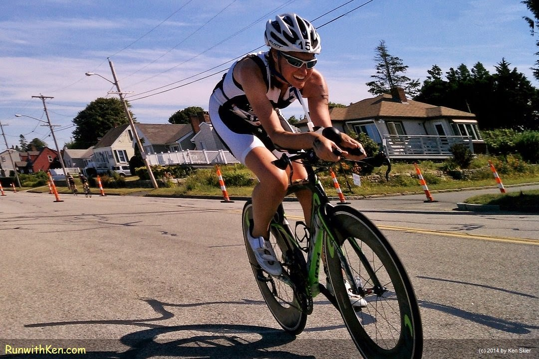 Up-close action photo of an aero cyclist, tucked low while bicycling at the Whaling City Triathlon in New Bedford, MA. Sports Photography from Inside the Pack by Ken Skier. (RunwithKen.com)