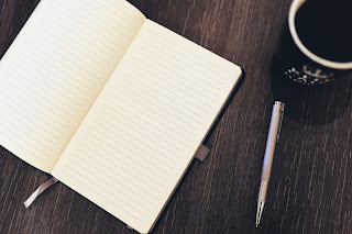 Blank notebook with pen and coffee mug